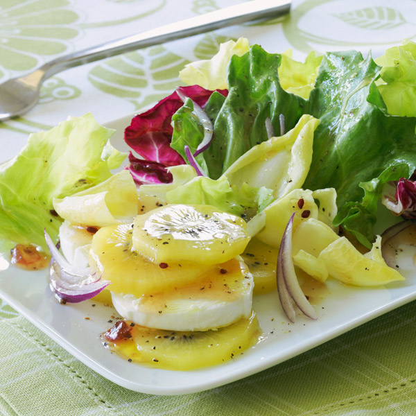 Mixed green salad with kiwis and goat cheese