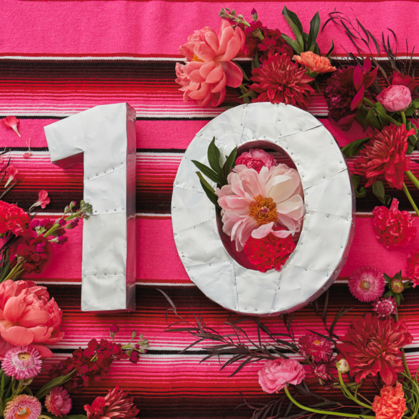 10-anniv-ideas A number ten (for 10th anniversary) made of hammered tin (a traditional 10th anniversary gift) against a pink striped background and surrounded by pink and red roses