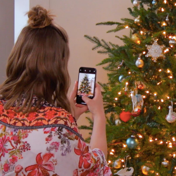 lady taking a picture of keepsake premium ornaments on a christmas tree