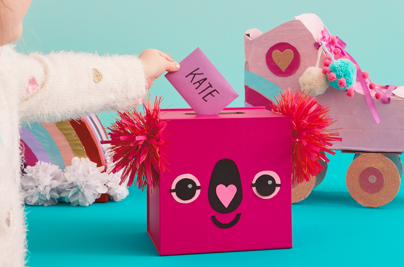 DIY Koala Valentine Box with childs hand on table with other Valentines