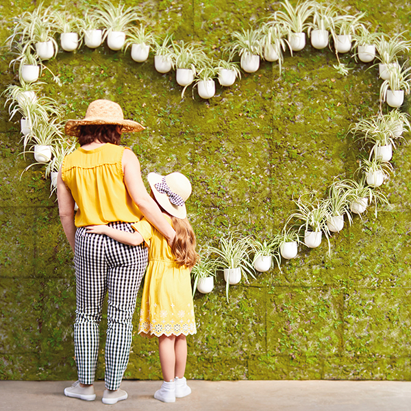 A mom and a child standing in front of plants shaped like a heart