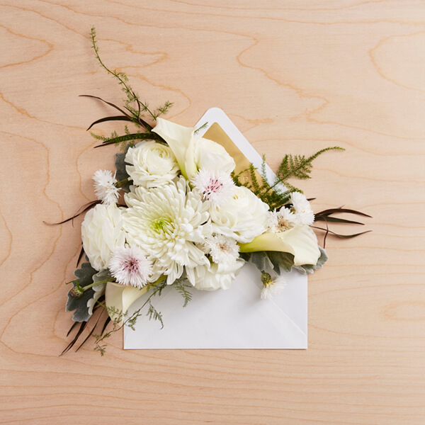 Sympathy card in envelope on table with flowers
