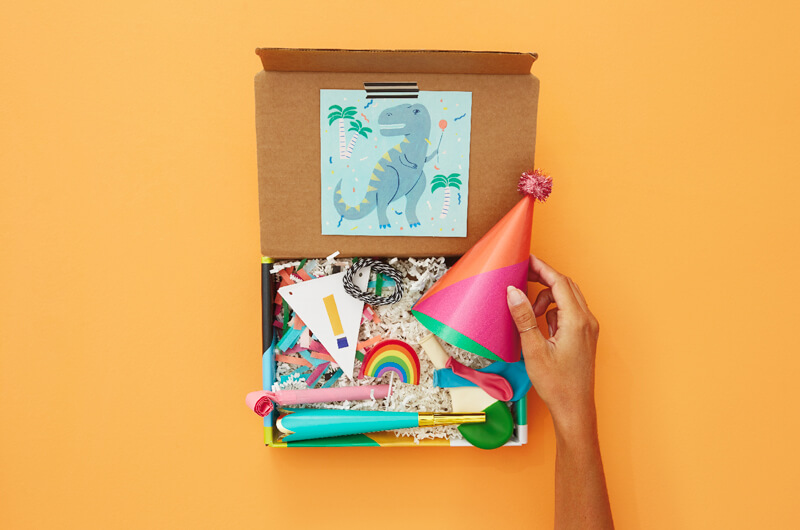 Hand putting birthday hat in birthday care package