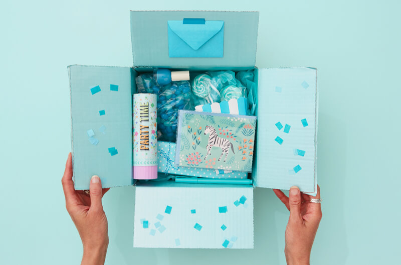Hands holding a blue birthday care package
