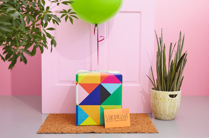 Birthday care package in front of door with balloon and envelope