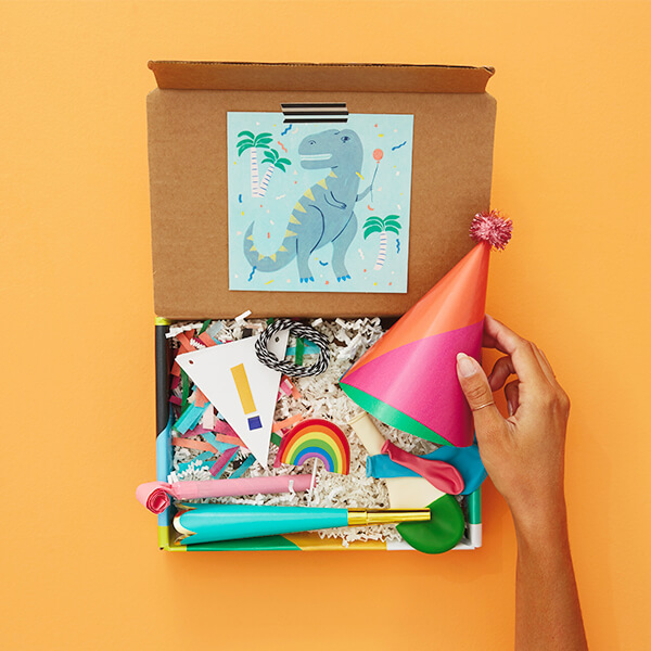 Hand putting party hat in birthday care package