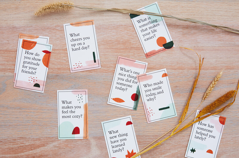 Gratitude conversation starter cards on table with wheat