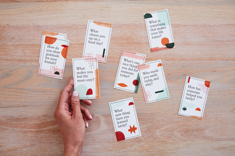 Hand holding gratitude conversation starter cards on table