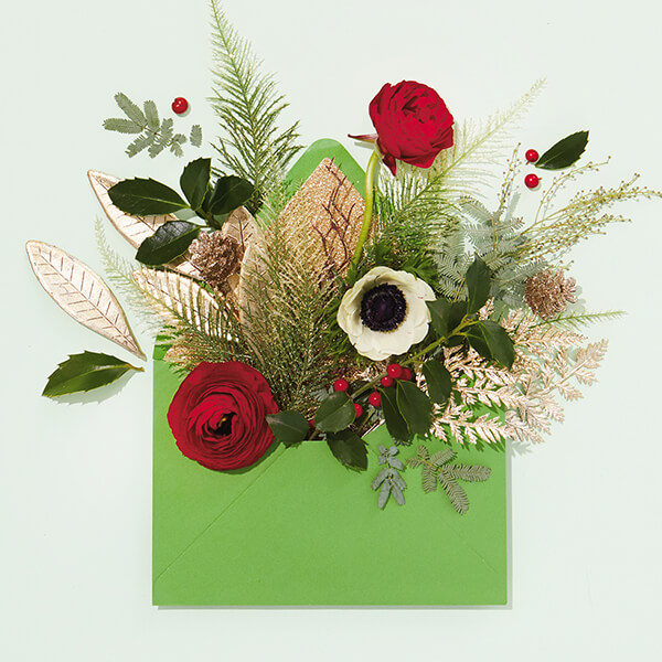 Christmas card with flowers coming out of envelope