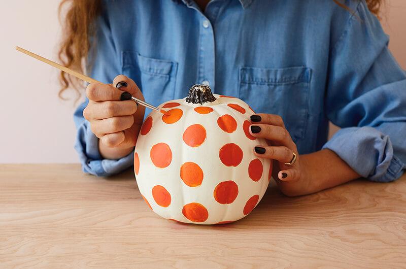 Painting a pumpkin with polka dots