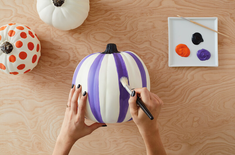 Painting a pumpkin with stripes