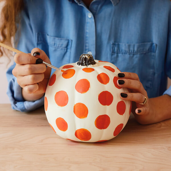 Crafting a painted pumpkin with polka dots