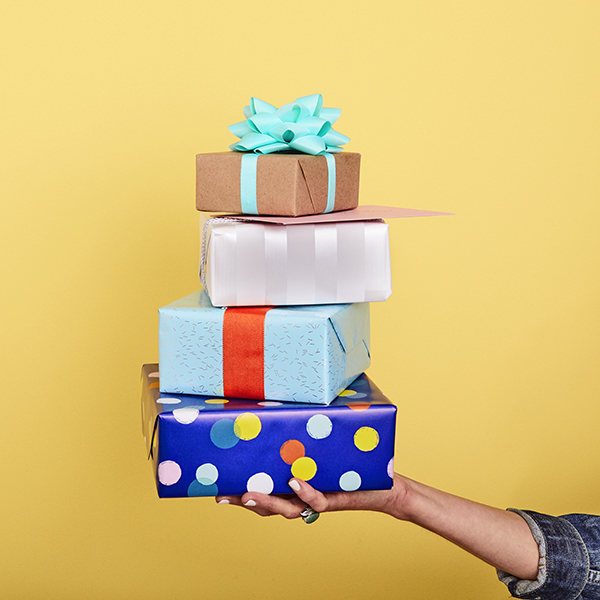 Hand holding four presents stacked with a card