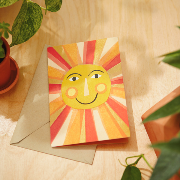 Encouragement Card with a sun on it and an envelope on a desk with plants