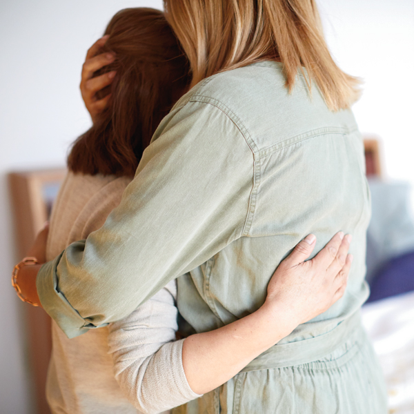 Two women embracing one another in comfort during tough time