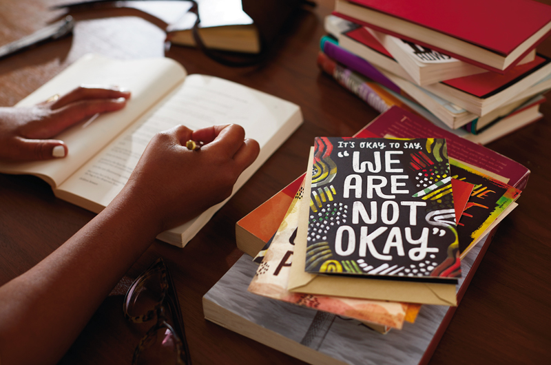 """Hand writing with card that says """"It's okay to say, 'We are not okay.'"""""""