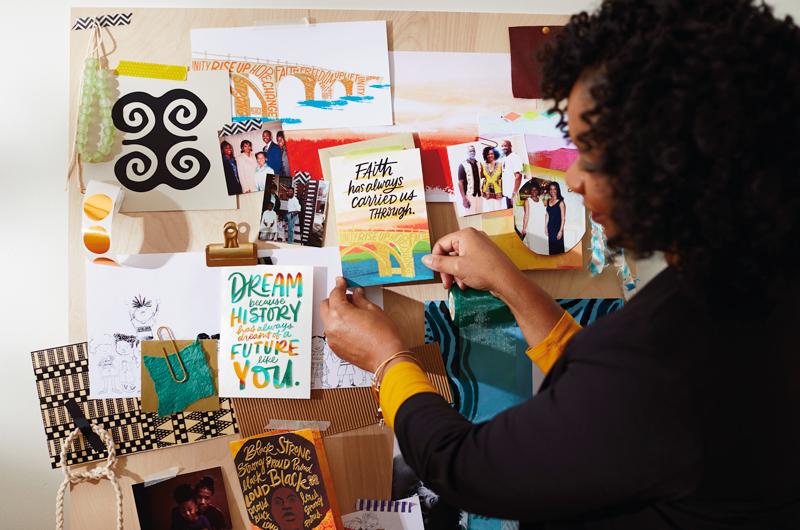 "Editorial Director Dierdra (""Dee"") Zollar with cards on art board"