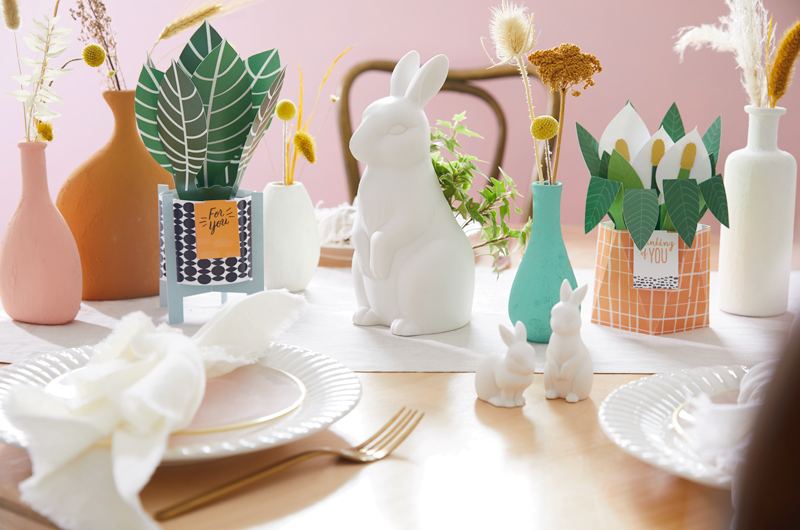 Easter table with cards, bunnies, vases and flatware