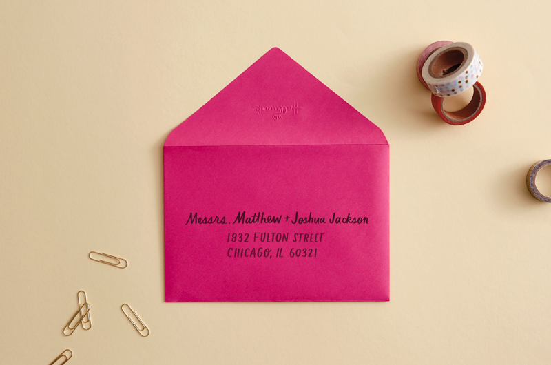 envelope on desk with pen that reads