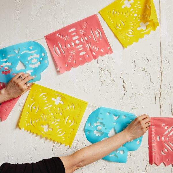 Papel Picado on white background with hands