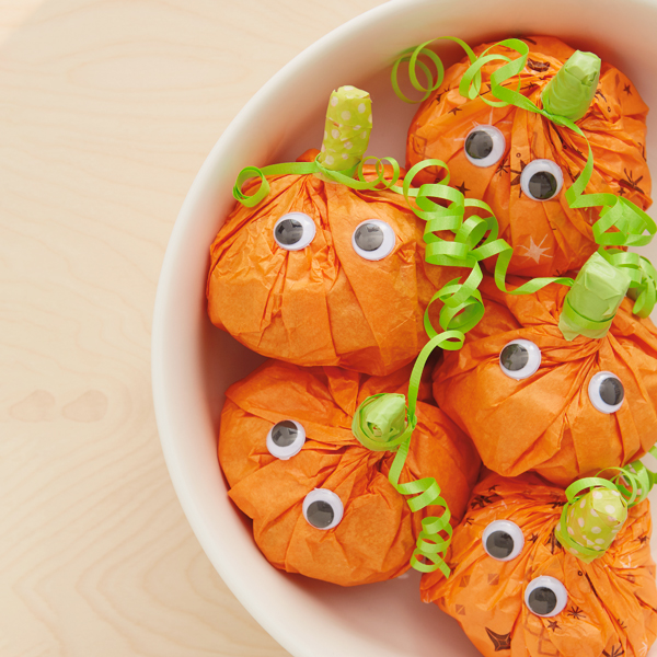 Pumpkin treat bags in a bowl for Halloween