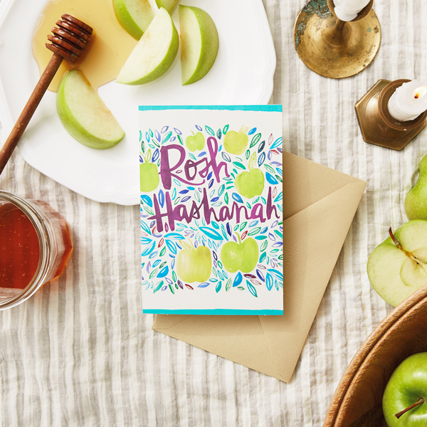 Rosh Hashanah Card on a table with apples, honey and candles
