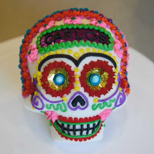 Front view of decorated sugar skull with gold foil eyes and royal icing embellishments in red, pink, green, blue and purple.