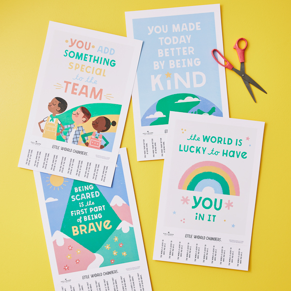 Inspirational posters on a yellow table with scissors