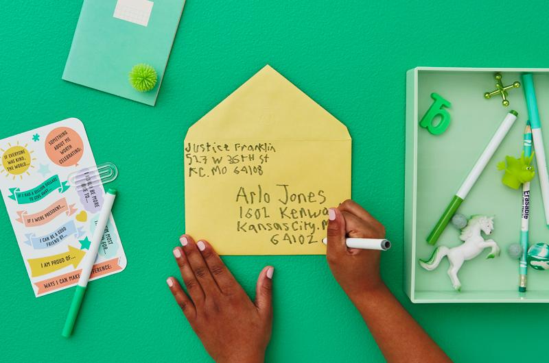 Kid writing address on envelope