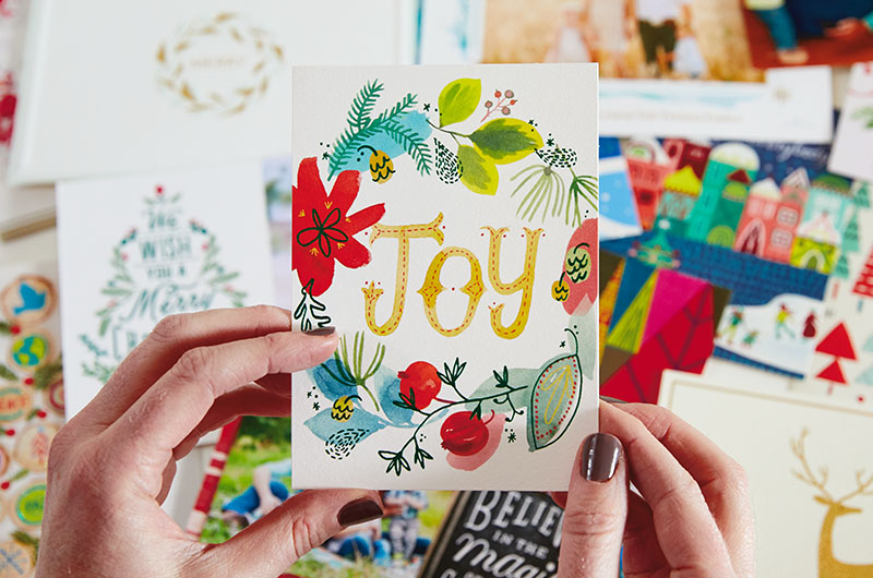Hands holding a Christmas card with JOY on the cover.