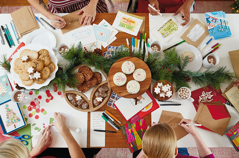 Overhead photo of a table covered in cards, envelopes, craft supplies and snacks; hands shown signing and decorating envelopes and cards.