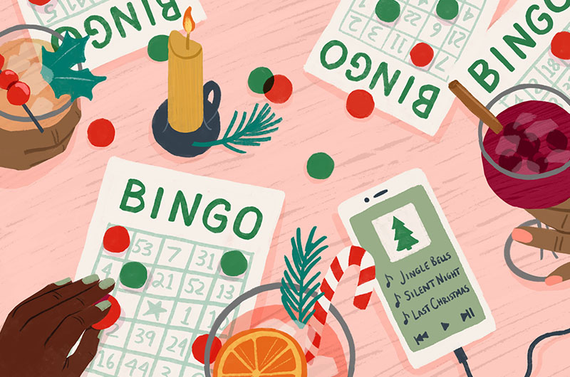 Christmas bingo sheets on a table with holiday cocktails